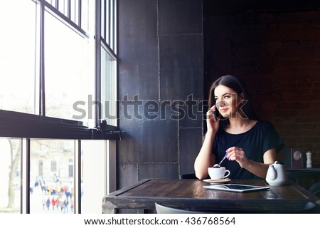 Young attractive girl talking on mobile phone and smiling while sitting alone in coffee shop during free time. Happy female having rest in cafe. Lifestyle - stock photo