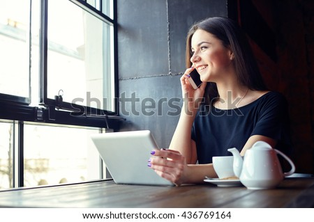 Young attractive girl talking on mobile phone and smiling while sitting alone in coffee shop during free time and working on tablet computer. Happy female having rest in cafe. Lifestyle - stock photo