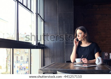 Young attractive girl talking on mobile phone and smilling while sitting alone in coffee shop during free time. happy female having rest in cafe. Lifestyle, coffee - stock photo