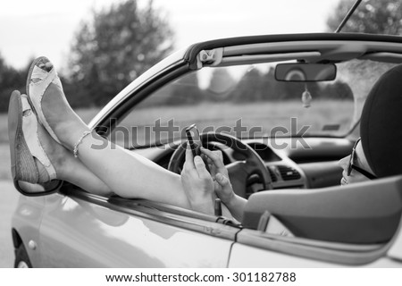Young attractive girl using mobile phone in her car.She is wearing black glasses and white sandals.Mobile phone is black,while coupe cabriolet is bright blue. Focus on glasses.Black and white photo.  - stock photo