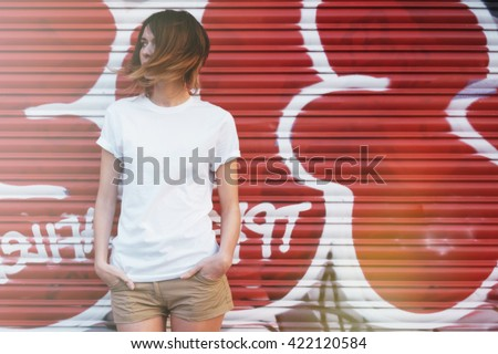 young attractive girl wearing a white t-shirt posing on a graffiti wall background  - stock photo