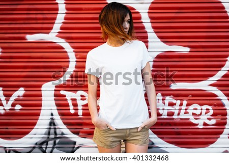young attractive girl wearing a white t-shirt standing on a graffiti wall background  - stock photo