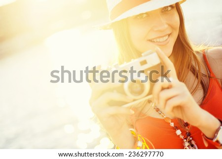 Young attractive girl with a camera - stock photo