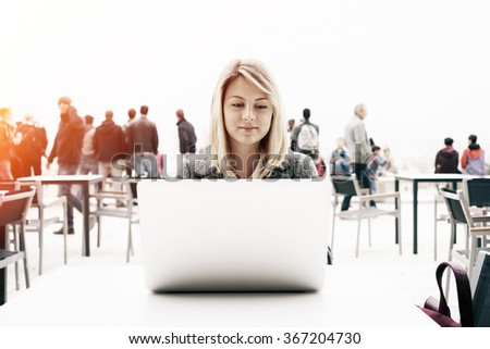 young attractive girl with blonde hair working with a laptop computer outside. Beautiful businesswoman searching information on the Internet - stock photo