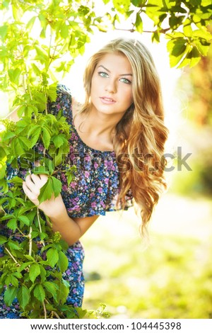 Young attractive girl with blue dress and blond hair outdoor on the field.Golden lady - stock photo