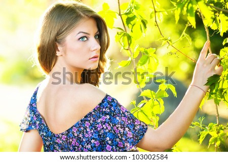 Young attractive girl with blue dress outdoor on the field. - stock photo
