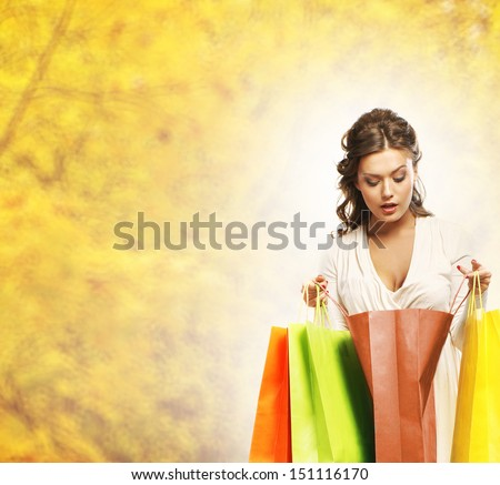 Young attractive girl with the shopping bags over autumn background - stock photo