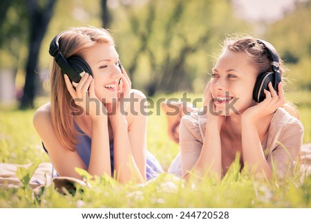 Young attractive girls in summer park wearing headphones - stock photo