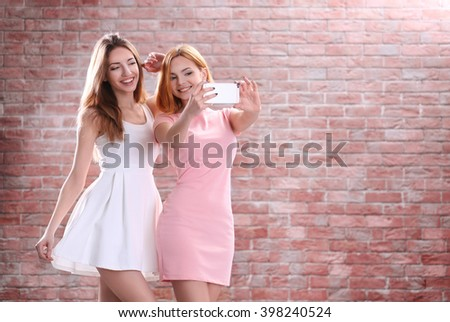 Young attractive girls taking selfie with mobile phone on brick wall background - stock photo
