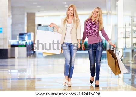 Young attractive girls with shopping bags - stock photo