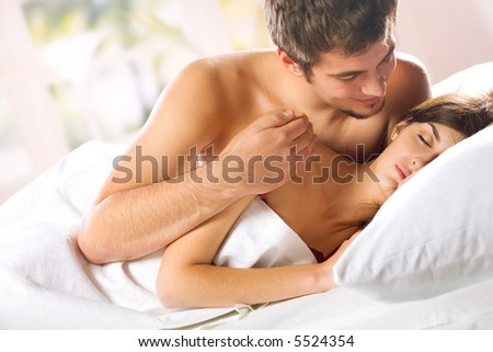Young attractive happy amorous couple in bedroom - stock photo
