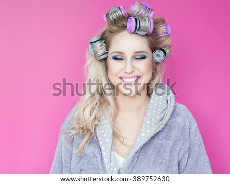 Young attractive happy blonde woman wearing a bathrobe with hot rollers beauty concept - stock photo