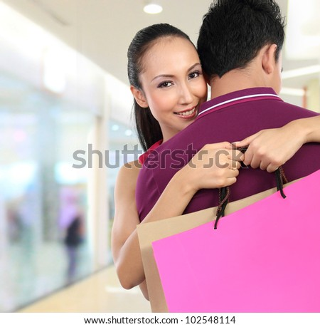 young attractive happy couple carrying shopping bag - stock photo