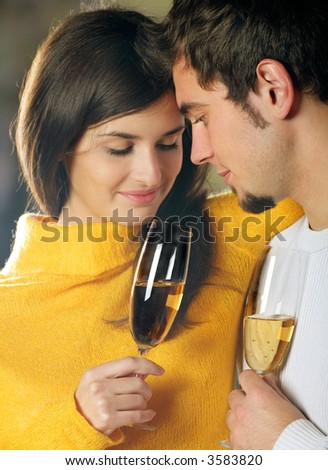 Young attractive happy couple celebrating event with champagne, outdoors - stock photo