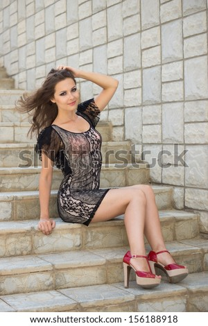 young attractive happy female sits on stairs, outdoor shoot