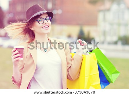 Young attractive happy shopper woman wearing hat and glasses holding shopping bags and take away coffee walking in the street  - stock photo