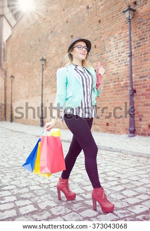 Young attractive happy shopper woman wearing hat and glasses holding shopping bags  walking in the street  - stock photo