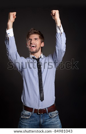 Young attractive happy smile business man stand and expressing success and victory concept, holding raised arms and hands up - stock photo