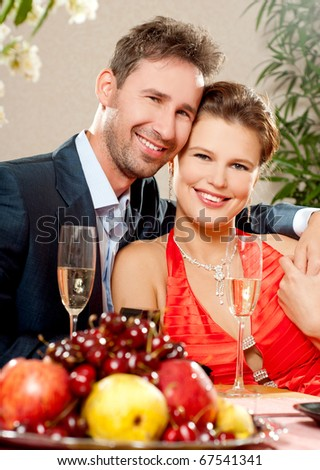 Young, attractive, happy, smiling couple celebrating with champagne, indoors - stock photo