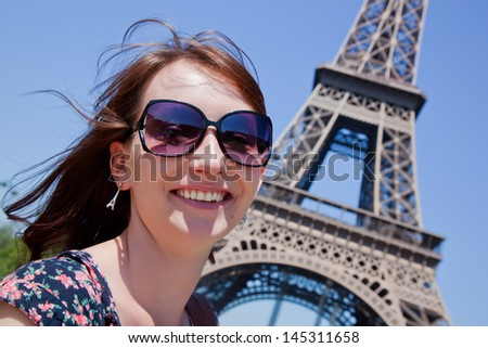 Young attractive happy woman standing and smiling against Eiffel Tower in Paris, France - stock photo