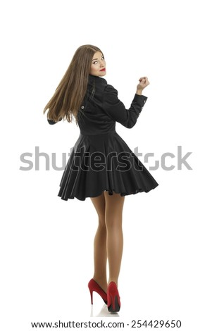 Young attractive happy woman, wearing black dress, spinning on red high heels shoes, isolated on white background. - stock photo