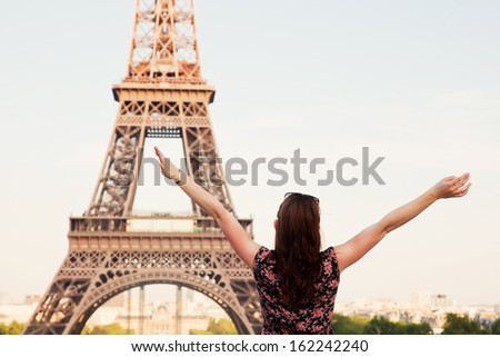 Young attractive happy woman with hands up facing the Eiffel Tower in Paris, France - stock photo