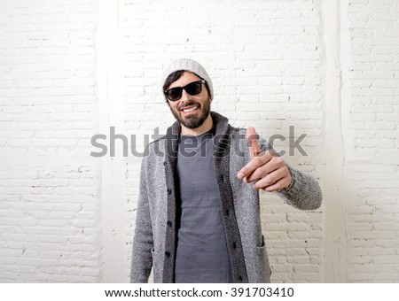 young attractive hipster and trendy style looking man smiling happy posing cool with attitude dressing informal wearing casual beanie beard and sunglasses in male fashion concept - stock photo