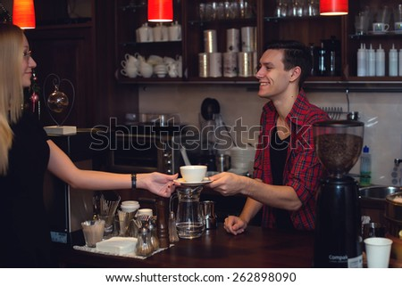 Young attractive hipster working in cafe as barista. Constant smiling providing perfect service giving order - stock photo