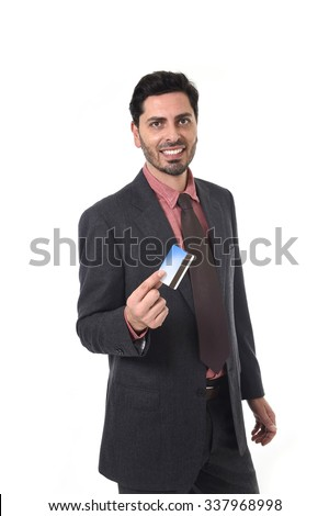 young attractive hispanic businessman in suit and tie looking happy and successful holding credit card in commerce and banking concept isolated on white background
