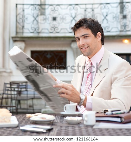 Young attractive hispanic businessman reading the newspaper while having breakfast at a coffee shop terrace in a classic city. - stock photo