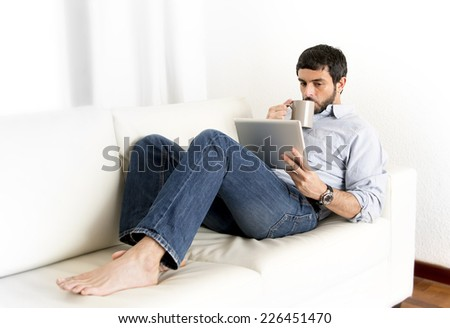 Young attractive hispanic man at home lying on white couch using digital tablet or pad looking relaxed drinking coffee at living room enjoying surfing internet watching online movie - stock photo