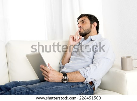 Young attractive hispanic man at home lying on white couch using digital tablet or pad looking thoughtful and pensive at living room internet surfing thinking about work project