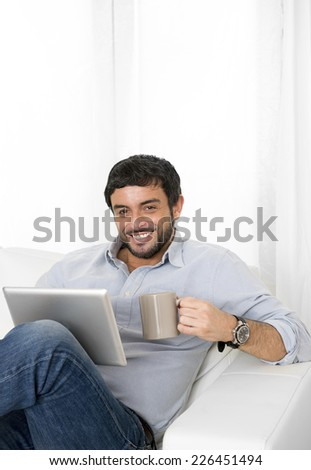 Young attractive hispanic man at home sitting on white couch using digital tablet or pad looking relaxed with coffee at living room enjoying surfing internet watching online movie