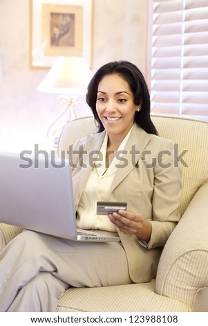 Young attractive Hispanic woman indoors sitting with a laptop and credit card making an on-line purchase