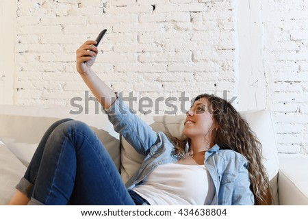 young attractive hispanic woman lying on home sofa couch alone taking selfie photo with mobile phone having fun enjoying and smiling happy shooting self portrait - stock photo