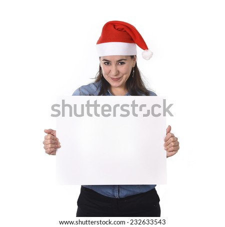 young attractive Hispanic woman wearing Santa Claus Christmas hat and blue shirt holding blank billboard or placard sign as copy space for adding corportate marketing isolated on white background