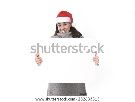 young attractive Hispanic woman wearing Santa Claus Christmas hat and winter jumper holding blank billboard or placard sign as copy space for adding text advertising isolated on white background