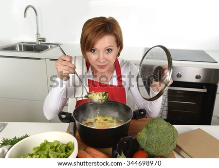 young attractive home cook woman in red apron at domestic kitchen holding saucepan with soup tasting delicious vegetable stew smiling satisfied in lifestyle and amateur cooking success - stock photo