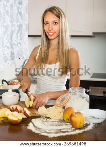 Young attractive housewife cooking apple pie at domestic kitchen - stock photo