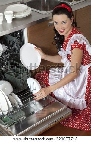 Young attractive housewife loads the dishes in the dishwasher