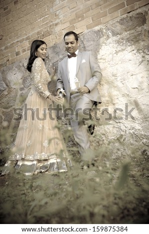 Young attractive indian couple standing by white double doors in garden