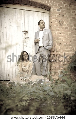 Young attractive indian couple standing by white double doors in garden - stock photo