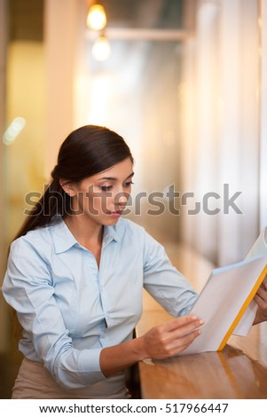Young Attractive Indian Woman Reading Book in Cafe
