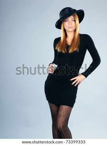 Young attractive killer widow over grey background - stock photo