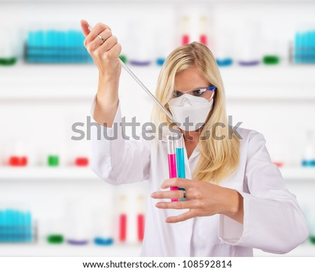 Young attractive laboratory assistant dropping chemical liquid into glass vials - stock photo
