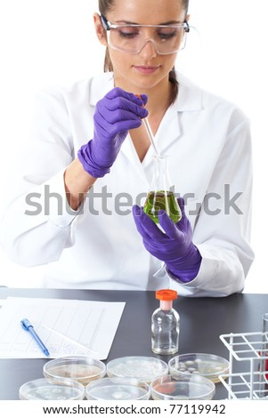 young attractive laboratory assistant makes some lab tests, petri dishes in front of her, while she works on test tube with green liquid, isolated on white - stock photo