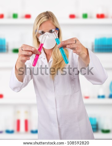 Young attractive laboratory assistant researching test tubes - stock photo