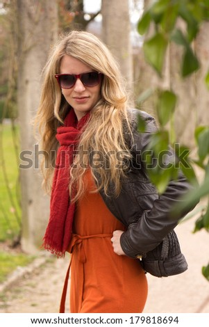 Young attractive lady in orange dress and sunglasses in the park - stock photo