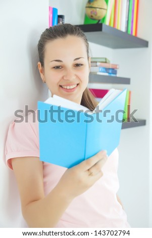 Young attractive lady sitting with a book
