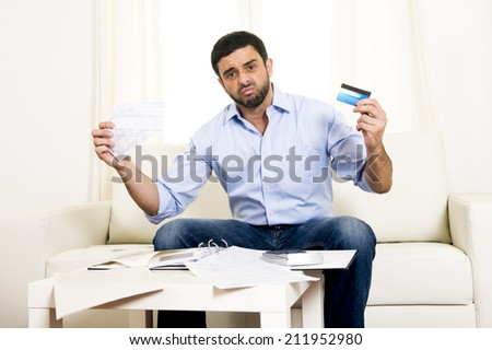 young attractive latin american business man at home sitting on sofa in stress with credit card and calculator accounting debts, bills and bank papers worried for money and financial situation - stock photo